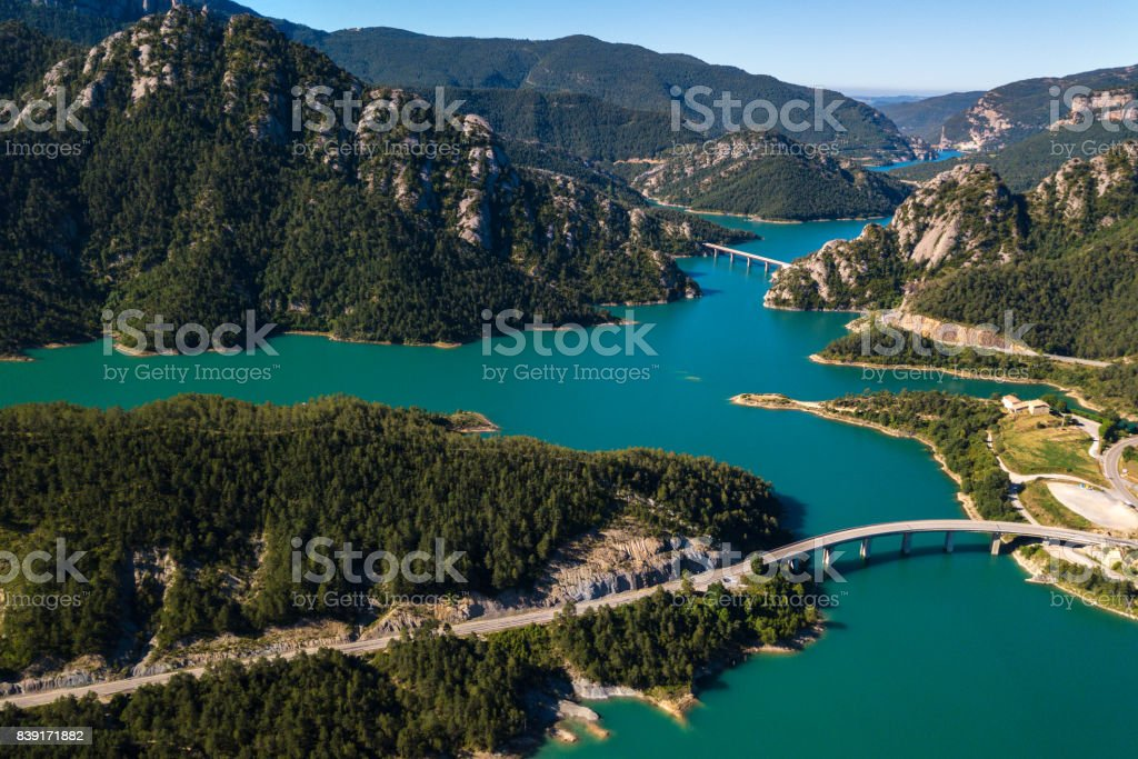 Aerial view of beautiful turquoise lake in mountains and several bridges across it. stock photo