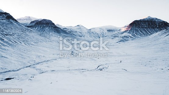 Drone photo of scenic highway road with snowy surroundings, fjord and mountain view, bright sunset above it and car driving through the road in the North Iceland