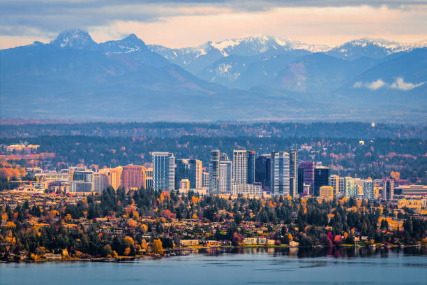 Aerial view of Bellevue, Washington Bellevue, Washington. The snowy Alpine Lakes Wilderness mountain peaks rise behind the urban skyline. washington state stock pictures, royalty-free photos & images