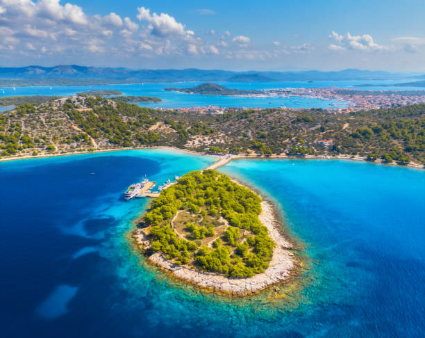 Aerial view of beutiful small island in sea bay at sunny day in summer in Murter, Croatia. Top view of transparent blue water, green trees, mountain, sandy beach, boats and yachts. Tropical landscape stock photo
