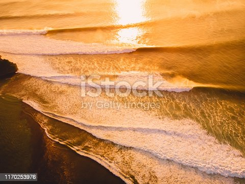 843079528istockphoto Aerial view of big stormy waves at warm sunset. Golden colors 1170253976