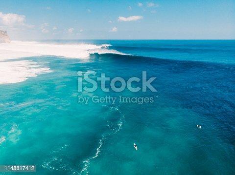 843079528istockphoto Aerial view of big wave surfing in Bali. Big waves in ocean 1148817412