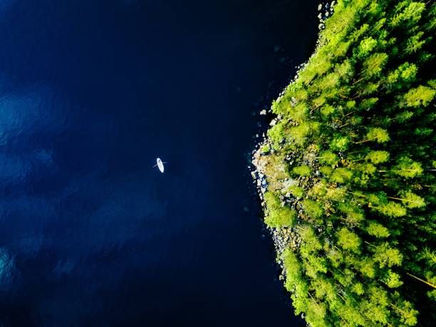 Aerial view of blue lake with a fishing boat and green forests with rocks in Finland. Aerial view of blue lake with a fishing boat and green forests with rocks on a summer day in Finland. antenna aerial stock pictures, royalty-free photos & images