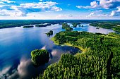 Aerial view of blue lakes and green forests on a sunny summer day in Finland. Drone photography from above