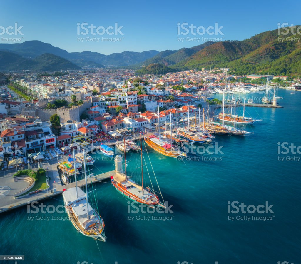 Aerial view of boats and beautiful architecture at sunset in Marmaris, Turkey. Colorful landscape with boats in marina bay, sea, city, mountains. Top view from drone of harbor with yacht and sailboat stock photo