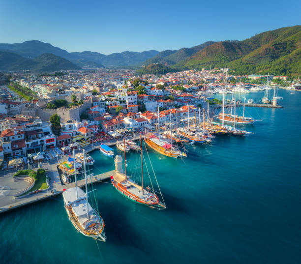 aerial view of boats and beautiful architecture at sunset in marmaris, turkey. colorful landscape with boats in marina bay, sea, city, mountains. top view from drone of harbor with yacht and sailboat - den belitsky foto e immagini stock