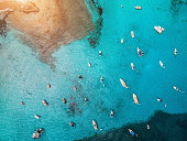 Aerial view of boats and luxury yachts in transparent blue sea at sunset in Spain. Colorful landscape with marina bay, azure water. Balearic islands. Top view. Travel in Europe. Summer vacation