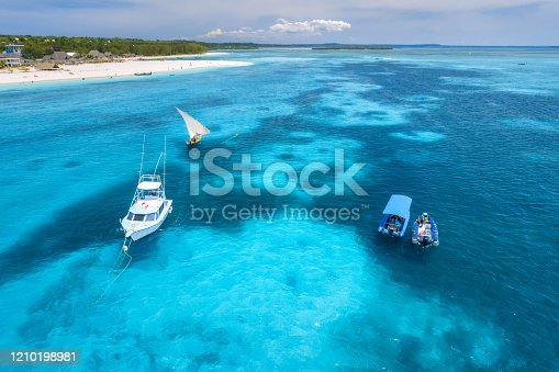 1136453253 istock photo Aerial view of boats and yachts on tropical sea coast with sandy beach at bright sunny day in summer. Indian Ocean in Africa. Landscape with boat, palm trees, clear blue water, sky. View from above 1210198981
