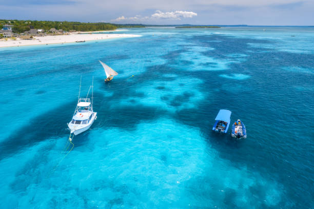 Aerial view of boats and yachts on tropical sea coast with sandy beach at bright sunny day in summer. Indian Ocean in Africa. Landscape with boat, palm trees, clear blue water, sky. View from above stock photo