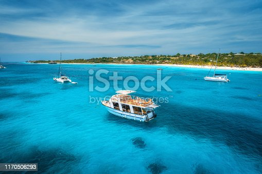 1136453253 istock photo Aerial view of boats and yachts on tropical sea coast with white sandy beach at bright sunny summer day . Indian Ocean in Africa. Landscape with boat, palm trees, transparent blue water, sky. Top view 1170506293
