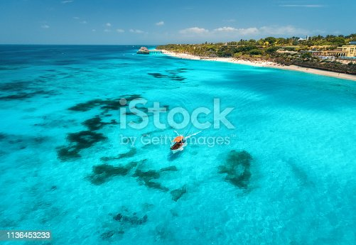 1136453253 istock photo Aerial view of boats on tropical sea coast with sandy beach at sunny day. Summer holiday on Indian Ocean, Zanzibar, Africa. Landscape with boat, palm trees, transparent blue water, hotels. Top view 1136453233