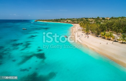 1136453253 istock photo Aerial view of boats on tropical sea coast with sandy beach at sunny day. Summer holiday on Indian Ocean, Zanzibar, Africa. Landscape with boat, palm trees, transparent blue water, hotels. Top view 1136453235