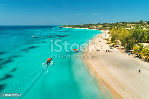 1136453253 istock photo Aerial view of boats on tropical sea coast with sandy beach at sunny day. Summer holiday on Indian Ocean, Zanzibar, Africa. Landscape with boat, palm trees, transparent blue water, hotels. Top view 1136453240