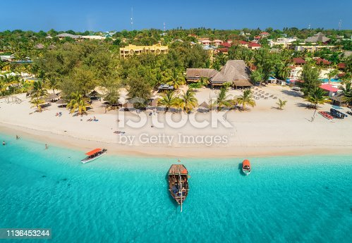 1136453253 istock photo Aerial view of boats on tropical sea coast with sandy beach at sunny day. Summer holiday on Indian Ocean, Zanzibar, Africa. Landscape with boat, palm trees, transparent blue water, hotels. Top view 1136453244