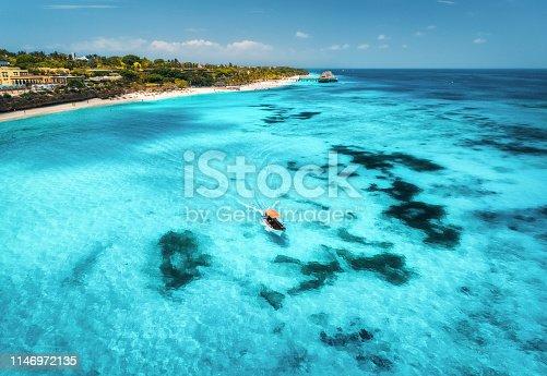 1136453253 istock photo Aerial view of boats on tropical sea coast with sandy beach at sunny day. Summer holiday on Indian Ocean, Zanzibar, Africa. Landscape with boat, palm trees, transparent blue water, hotels. Top view 1146972135