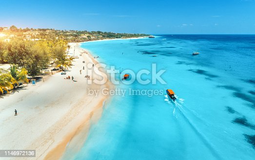 1136453253 istock photo Aerial view of boats on tropical sea coast with sandy beach at sunset. Summer holiday on Indian Ocean, Zanzibar, Africa. Landscape with boat, palm trees, transparent blue water, hotels. Top view 1146972136