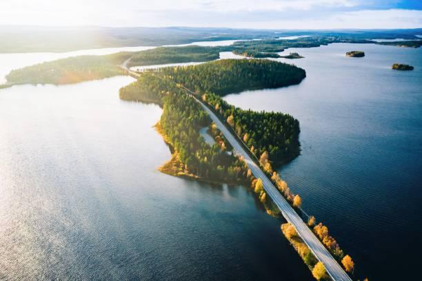 Luftaufnahme der Brücke über blaue Seen mit Sonnenlicht im bunten Herbstwald in Finnland. – Foto