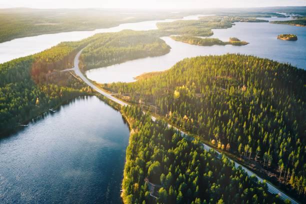 핀란드의 다채로운 가을 숲에서 태양 빛이있는 푸른 호수를 가로 지르는 다리의 공중 보기. - 핀란드 뉴스 사진 이미지