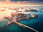 istock Aerial view of bridge over the sea and mountains in Lofoten Islands, Norway. Henningsvaer at sunset in winter. landscape with azure water, sky with gold sunlight, rocks, buildings, road. Top view 1093755566