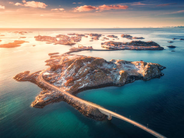 Aerial view of bridge over the sea and mountains in Lofoten Islands, Norway. Henningsvaer at sunset in winter. landscape with azure water, sky with gold sunlight, rocks, buildings, road. Top view Aerial view of bridge over the sea and mountains in Lofoten Islands, Norway. Henningsvaer at sunset in winter. landscape with azure water, sky with gold sunlight, rocks, buildings, road. Top view lofoten stock pictures, royalty-free photos & images