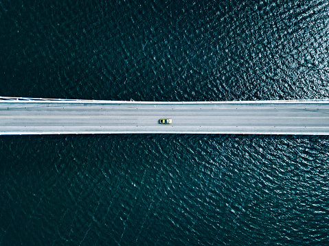 Aerial view of bridge road with cars over lake or sea in Finland
