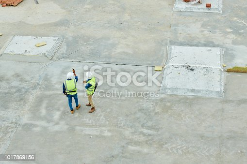Drone view of two unrecognizable men in helmets and waistcoats inspecting construction site together