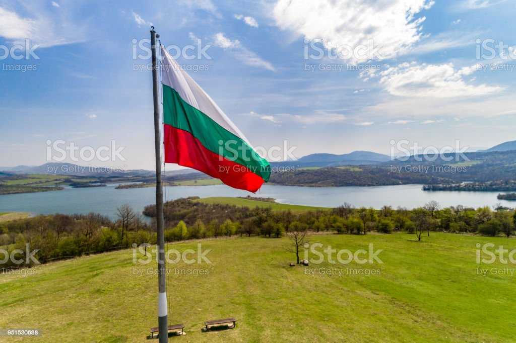 Aerial view of Bulgarian national flag waving proudly in front of a gorgeous landscape with lake and mountains stock photo