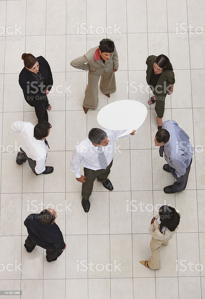 Aerial View of businessman standing in center of businesspeople with speech balloon royalty-free stock photo