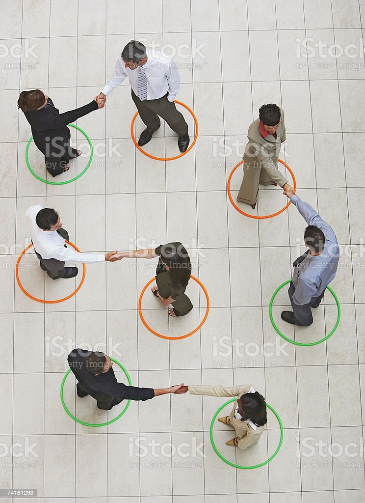 Aerial view of businesspeople standing in circles shaking hands royalty-free stock photo