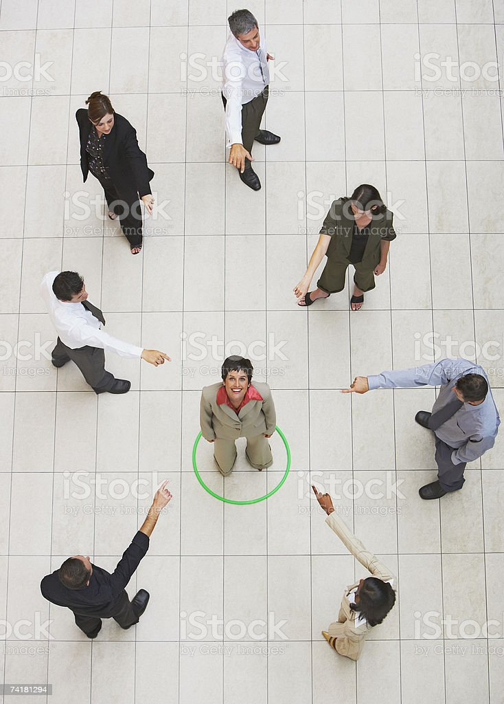 Aerial View of businesswoman standing in circle with businesspeople pointing royalty-free stock photo