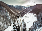 Drone shot depicting one car driving on a narrow road through the mountainous wilderness. The land either side of the road is covered with snow and dotted with fur trees. A stream also courses through the frame. Room for copy space.