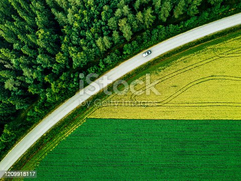Aerial view of car driving on road along the green forest and potato with yellow rapeseed fields in rural landscape in summer Finland.