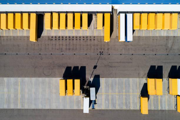 aerial view of cargo containers and distribution warehouse - prodotti supermercato foto e immagini stock