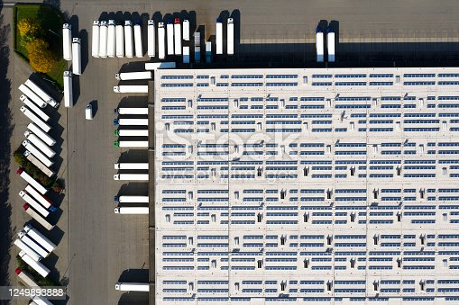 Aerial view of cargo containers, semi trailers, industrial warehouse, storage building and loading docks, renewable energy plants, Bavaria, Germany.
