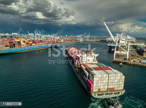 Aerial shot of a massive cargo ship arriving in the Port of Long Beach, California.