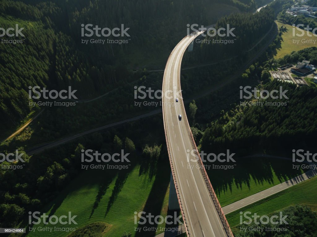 aerial view of cars passing bridge over beautiful green forest - Zbiór zdjęć royalty-free (Architektura)