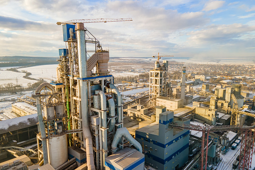 Cement plant with high factory structure and tower crane at industrial production area.