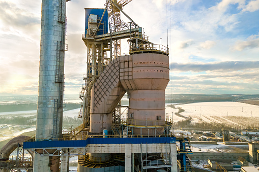 Aerial view of cement plant with high factory structure and tower crane at industrial production area.