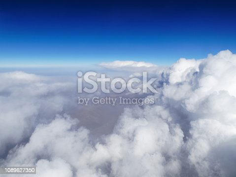istock Aerial view of cloud and sky with airplane wing from airplane window ,Traveling concept. 1089627350