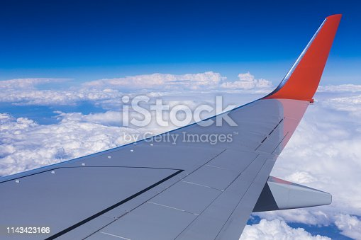 155439315istockphoto Aerial view of cloud blue sky and plane wing view through the airplane window. 1143423166