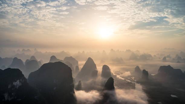 Luftaufnahme des Wolkengebilde über Ackerland und Berg am Morgen – Foto