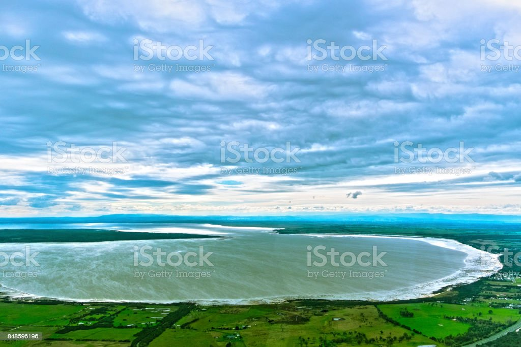 Aerial view of coastal bay (inlet) with distant hills, farmland stock photo