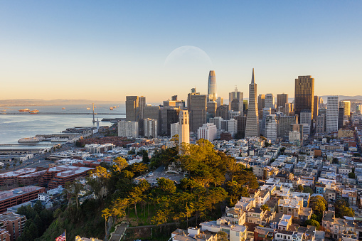 Aerial view of Coit Tower and the San Francisco financial district in the background. Bay Bridge and several landmarks fill the background.