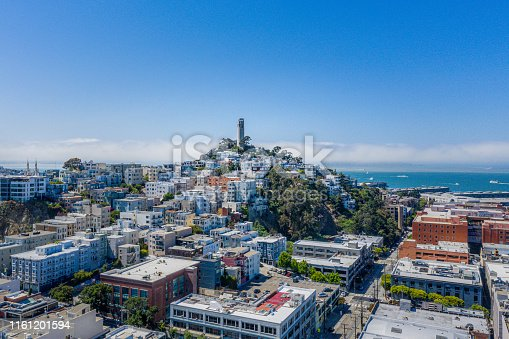 An aerial view of Coit Tower on a beautiful blue sky day. The San Francisco Bay is in the background dotted with boats.