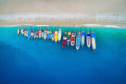 Aerial view of colorful boats in mediterranean sea in Oludeniz, Turkey. Beautiful summer seascape with ships, clear azure water and sandy beach in sunny day. Top view of yachts from flying drone