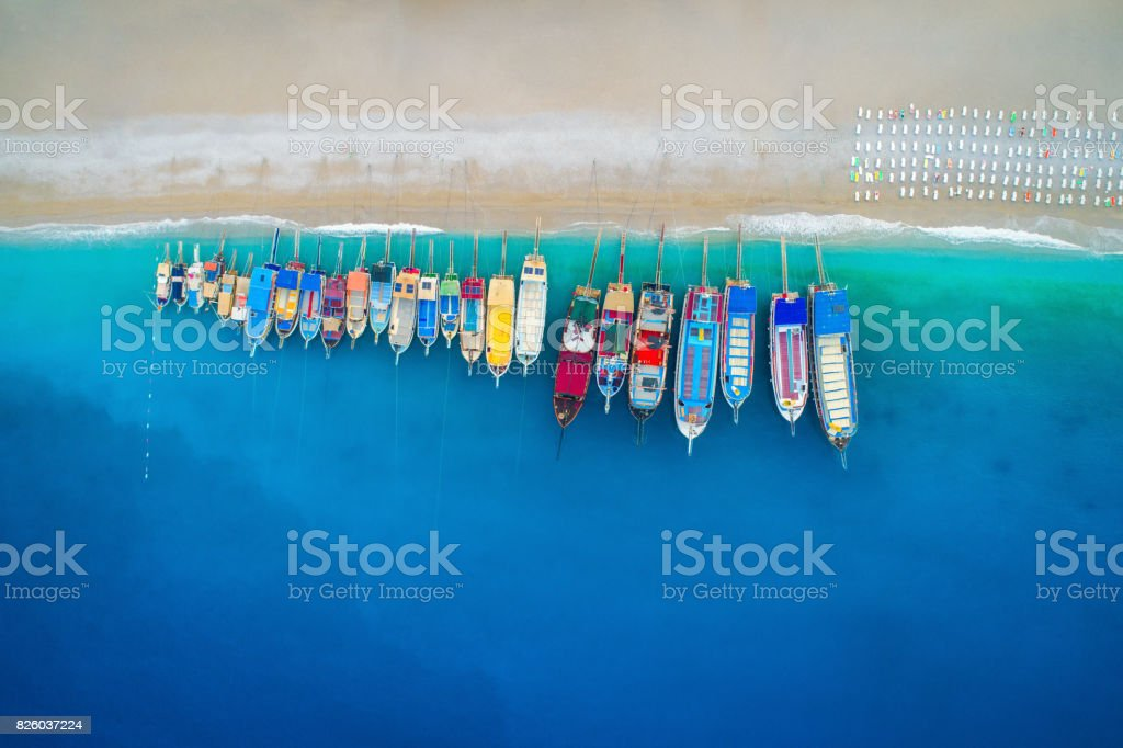 Aerial view of colorful boats in mediterranean sea in Oludeniz, Turkey. Beautiful summer seascape with ships, clear azure water and sandy beach in sunny day. Top view of yachts from flying drone stock photo