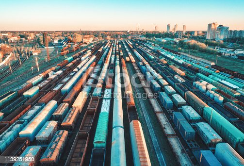 Aerial view of colorful freight trains on railway station at sunset. Wagons with goods on railroad. Heavy industry. Industrial scene with cargo trains, city buildings. Top view from drone. Vintage