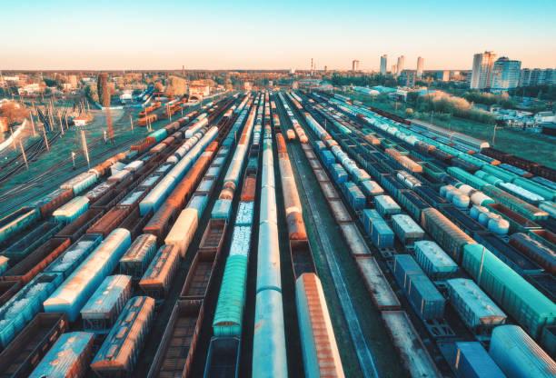 在日落時, 在火車站上可以看到五顏六色的貨運列車的鳥圖。鐵路上有貨物的貨車。重工業。工業場景與貨運列車, 城市建築。無人機的頂視圖。老式 - 火車車廂 個照片及圖片檔