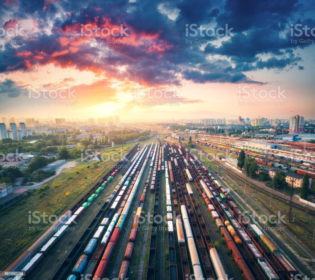 Aerial view of colorful freight trains. Railway station. Wagons with goods on railroad. Cargo trains. Heavy industry. Industrial scene with trains, city buildings and cloudy sky at sunset. Top view stock photo
