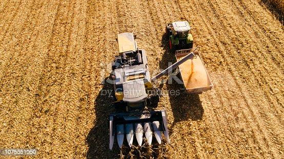1072634078 istock photo Aerial view of combine corn harvester unloading autumn harvest 1075551050